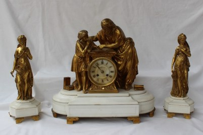 A 19th century French ormolu and marble clock garniture, in the form of a scholar and pupil studying from a book, with books at their feet. Sold at Anthemion Auctions for £780