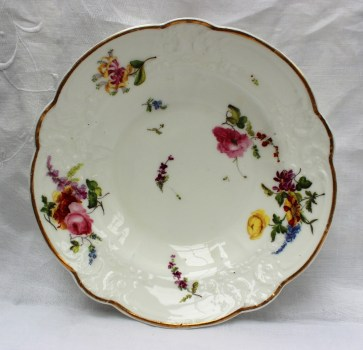 "A Nantgarw porcelain bowl, with a gilt line decorated rim, a moulded border painted with sprays of garden flowers, marked ""NANT- GARW CW"", 20.8cm diameter. Sold for £650 at Anthemion Auctions"