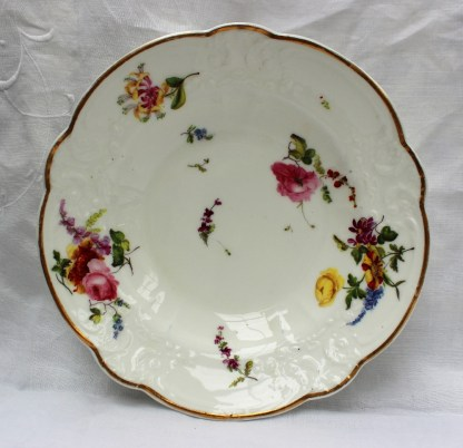 """A Nantgarw porcelain bowl, with a gilt line decorated rim, a moulded border painted with sprays of garden flowers, marked """"NANT- GARW CW"""", 20.8cm diameter. Sold for £650 at Anthemion Auctions"""