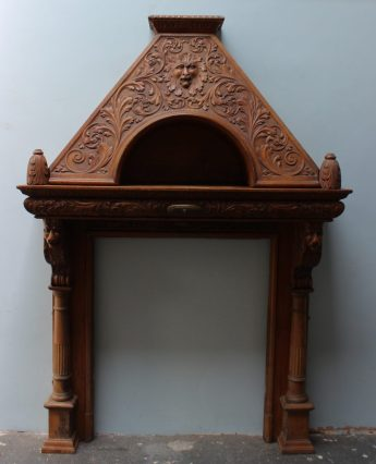A 19th century oak fire surround carved with lions masks and scrolling leaves , the base supported with lion heads and stop fluted columns on a square base. Sold for £620 at Anthemion Auctions