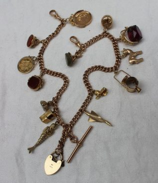 A 9ct gold Albert chain with multiple charms. Sold at Anthemion Auctions for £750
