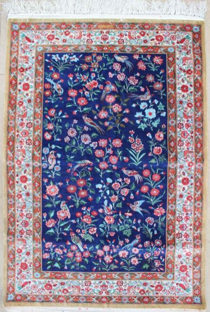 A silk rug, with a dark blue ground decorated with sprays of flower and birds, with three guard stripes of flowers and birds. Sold at Anthemion Auctions for £680