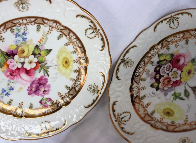 A pair of Swansea porcelain plates with a raised moulded rim with gilt and green highlights, the inner ring with gilt cross hatched decoration painted to the centre with sprays of garden flowers. Sold for £600 at Anthemion Auctions