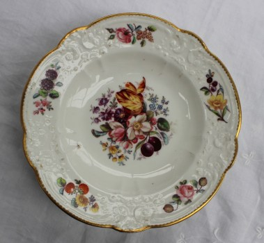 "A Nantgarw porcelain plate with a scalloped edge and moulded border painted with single flowers, painted to the centre with a spray of garden flowers, marked ""NANT- GARW C W"". Sold for £600 at Anthemion Auctions"