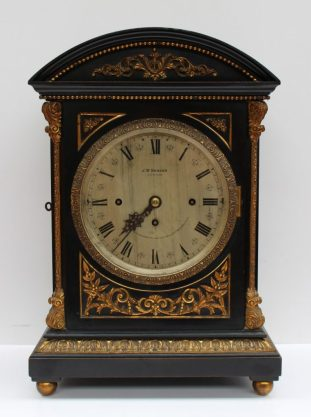 An early 20th century ebonised bracket clock, the domed top with gilt metal beading and leaf decoration with leaf cast columns, a gilt leaf base on ball feet, the silvered dial with Roman numerals inscribed J.W Benson, London, By Royal Appointment to her late Majesty Queen Victoria. Sold for £1,450 at Anthemion Auctions