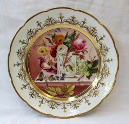 A Nantgarw porcelain plate with a scalloped edge, the border with gilt flower heads and leaves, painted to the centre with a vase of flowers, grapes and leaves on a marble plinth. Sold for £2,500 at Anthemion Auctions