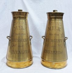 """A pair of small brass and white metal milk churns, of tapering cylindrical form with leaf cast handles, inscribed """"Milk for the nursery and invalids"""" 50cm high. Sold for £1,050 at Anthemion Auctions"""
