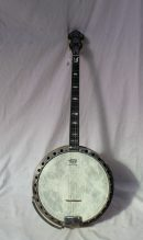 A Paragon four string banjo, with mother of pearl inlay and a veneered back and sides, 86cm long x 33cm diameter. Sold for £2,200 at Anthemion Auctions