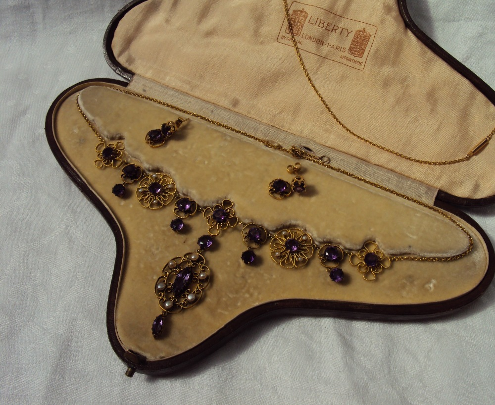 An amethyst and seed pearl necklace together with a pair of amethyst drop earrings, in a fitted leather box for Liberty, London and Paris. Sold at Anthemion Auctions for £1,450