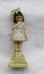 """A Royal Doulton figure - Shy Anne, HN60, in a pale blue dress with small blue flowers, standing on a yellow plinth base, printed """"SHY ANNE"""" marked to the underside with a green printed mark. Sold for £1,350 at Anthemion Auctions"""