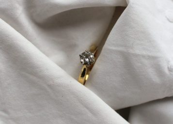 A solitaire diamond ring the brilliant cut stone approximately 0.5 of a carat to a white metal claw setting and 18ct yellow gold shank. Sold for £360 at Anthemion Auctions