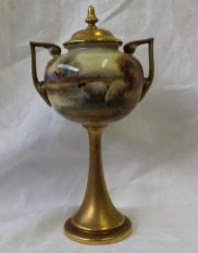 Lot 226 - Sold for £460 - A Royal Worcester porcelain two-handled pedestal vase and cover of urn form, shape No. 2736, painted with sheep by a lake, a cottage in the distance, and gilt, by Harry Davis, date code for 1924, 23 cms high