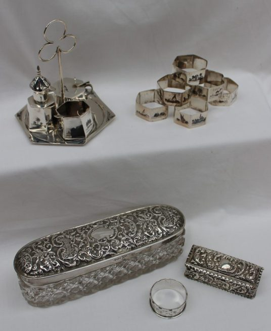 An Edward VII silver topped dressing table pot, Sheffield, 1906, Walker and hall, together with another silver dressing table pot, white metal niello decorated cruet and napkin rings weighable hall marked silver approximately 159 grams. Sold for £200 at Anthemion Auctions