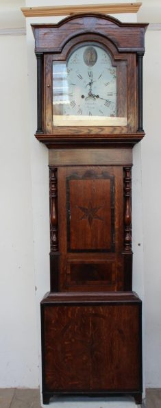 A 19th century oak and mahogany longcase clock, the domed hood with fluted ionic columns above a short trunk door, box base and bracket feet