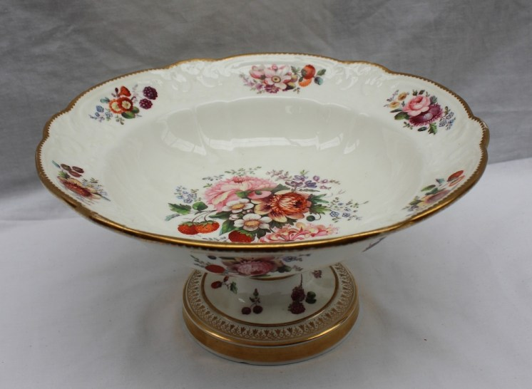 A Nantgarw open tureen painted with a central spray of flower heads and strawberries, the border painted with sprays of flowers to a moulded decoration and scalloped shell rim on a ring turned column and circular foot. Sold for £3,100 at Anthemion Auctions
