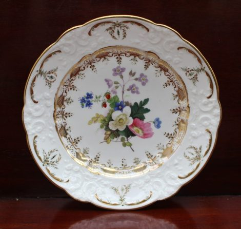 A Swansea porcelain plate, the border moulded with scrolls and flower heads, the centre painted with strawberries and garden flowers, iron red mark to the reverse, 21cm diameter. Sold for £620 at Anthemion Auctions