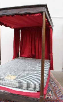 An 18th century oak four poster bed, with a moulded cornice above a shallow frieze, the front tapering cylindrical uprights and rear rectangular uprights, 196cm long x 132cm wide x 192cm high
