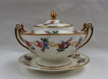 A Nantgarw sauce tureen cover and stand, of circular form with delicate spindle handles and a pointed pineapple finial picked out in gold, painted with sprays of garden flowers within a dentil gilt border, the stand with a continuous band of flowers and raised flower heads, the stand impressed NANT-GARW C.W.16cm high. Sold for £1,450 at Anthemion Auctions