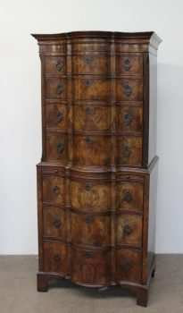 Lot 429 - Sold for £820 - A reproduction walnut chest on chest with a moulded serpentine top above four long graduated drawers, the base with a brushing slide and three long graduated drawers on bracket feet, 83.5cm wide x 187 cm high x 52cm deep