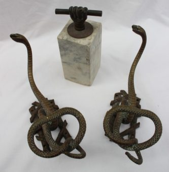 A pair of bronze snake coat hangers in the form of coiled snakes to a lattice back together with a marble doorstop with clenched fist handle