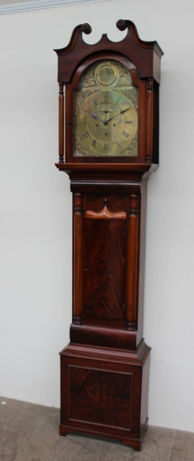 19th century mahogany longcase clock, the hood with a broken swan neck pediment and turned columns, above a long trunk door with an ogee arched top, box base and bracket feet. Sold for £470 at Anthemion Auctions