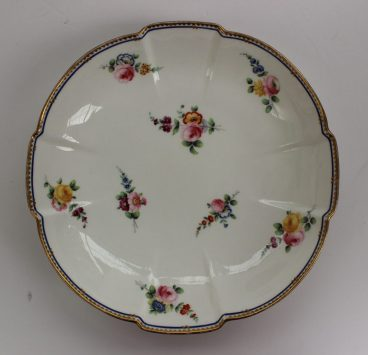 A Nantgarw cruciform dish in the sevres style, painted with flower heads and leaves, to a blue dash border, 22.5cm wide. Sold for £140 at Anthemion Auctions
