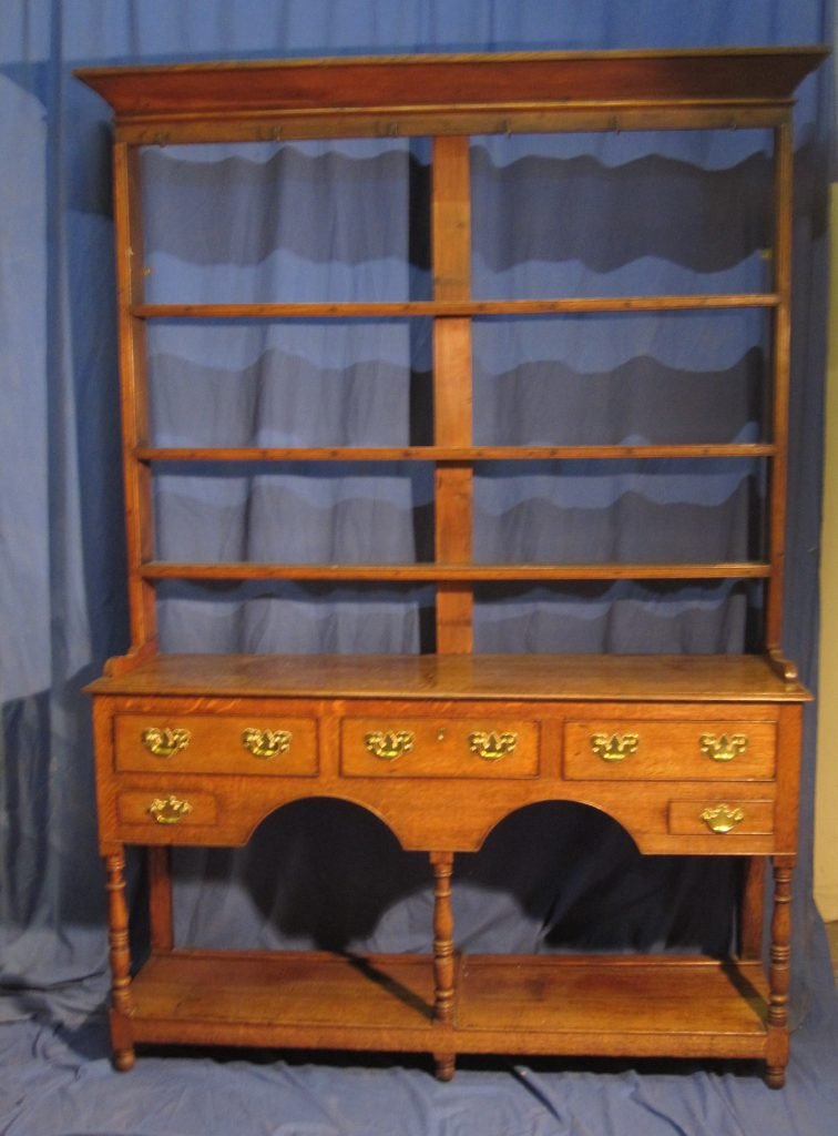 A 19th century South Wales dresser, the rack with moulded cornice above open shelves, the base with a planked top, five drawers, arched apron and a pot board on turned legs. 151 cms wide. Sold for £1,200 at Anthemion Auctions