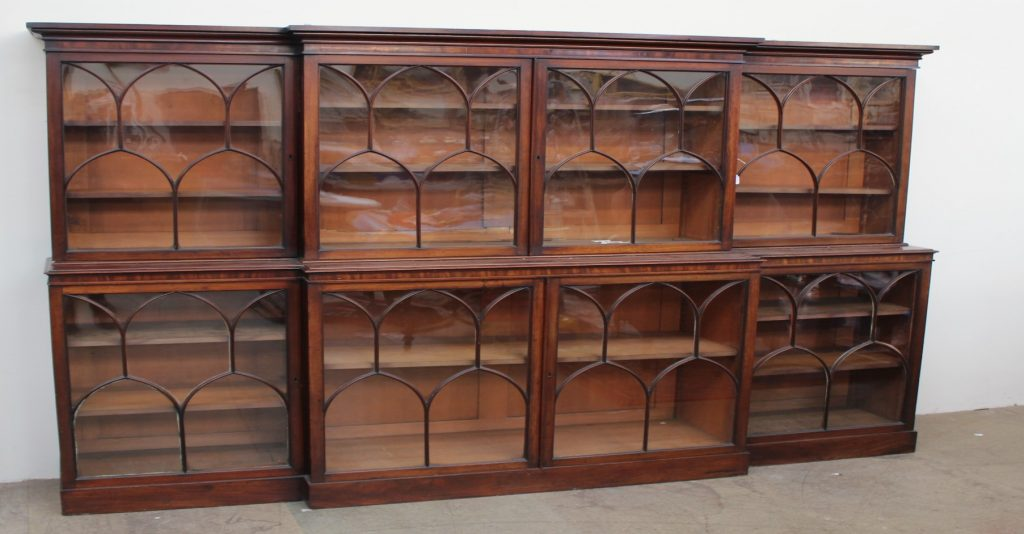 Lot 420 - Sold for £2,000 - A 19th century mahogany breakfront library bookcase, the moulded cornice above four glazed doors with arched glazing bars, the base with four glazed cupboards with similar glazing on a plinth base 234cm wide x 178cm high x 42cm deep