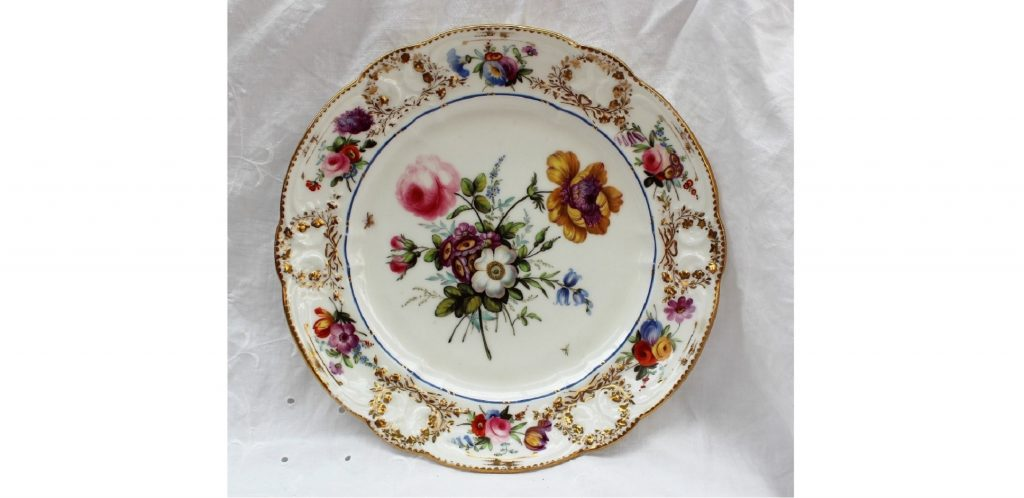Lot 281 - Sold for £2,800 - A Nantgarw plate, circa 1818-20, decorated in London, probably in the Bradley workshop. with an elaborate central floral spray with an anemone and rose flanked by insects in flight, a bright blue enamel line around the cavetto, the 'C' scroll border moulded with floral garlands picked out in gold, painted with floral sprays, impressed Nant-Garw C.W., 24.5cm diameter