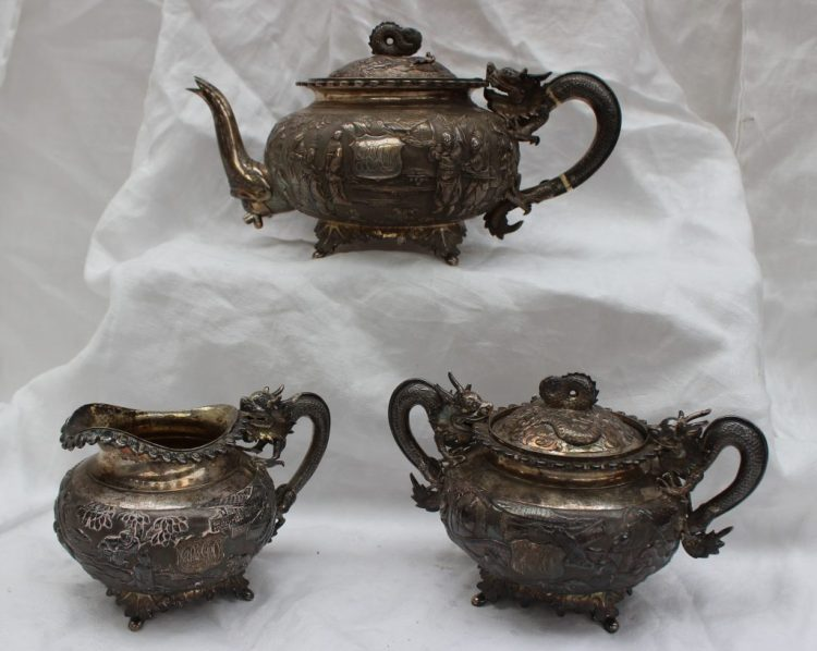 A Chinese silver three piece tea set, comprising a teapot, cream jug and twin handled sucrier and cover, each with dragon handles, the body cast with figures in a landscape on leaf cast feet, marked to the base of all pieces with a seal mark, the initials WHL 06, approximately 1580 grams. Sold for £5,500 at Anthemion Auctions