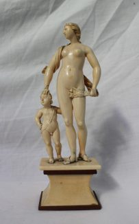 A 19th century ivory figure group of a naked maiden, with a swag of cloth concealing her modesty, with her hand on the head of a cherub on a plinth base, 22.5cm high. Sold for £1,300 at Anthemion Auctions