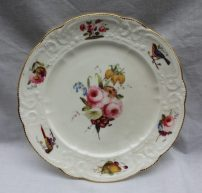 A Nantgarw porcelain plate painted to the centre with a spray of garden flowers, the rim painted with flowers and birds between a moulded edge and gilt scalloped rim, impressed 'NANT-GARW C.W.', 22cms diameter. Sold for £1,300 at Anthemion Auctions