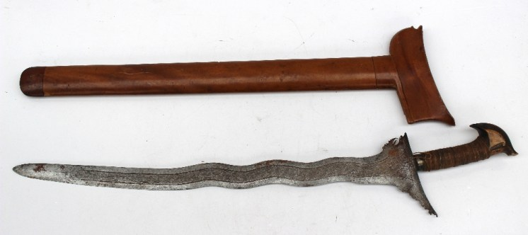 A Malay Kriss with a hardwood and cord coated grip, and an engraved waved blade in a scabbard, 67 cm long. Sold for £1,100 at Anthemion Auctions