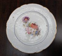"""A Nantgarw porcelain plate, with a C scroll border and dentil gilt rim, painted with a sprig of garden flowers to the centre with scattered butterflies, impressed """"NANT-GARW, C.W."""" to the base, 25cm diameter. Sold for £1,200 at Anthemion Auctions"""