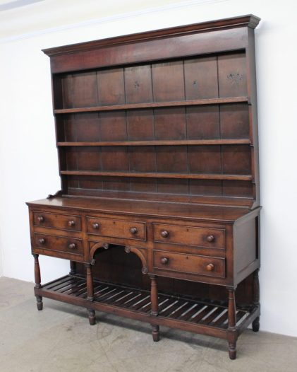 An 18th century South Wales oak dresser, the moulded cornice above three shelves, the base with an arrangement of five drawers on turned legs united by a pot board, 188cm wide x 49cm deep x 218cm high. Sold for £800 at Anthemion Auctions