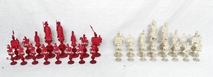 A 19th century Chinese carved Ivory chess set, natural and stained red, the figures in traditional Chinese dress on a puzzle ball and stepped circular base, Knights on horseback and the rooks as elephants, King 21.2cm high, Pawn 10.7cm high. Sold for £950 at Anthemion Auctions