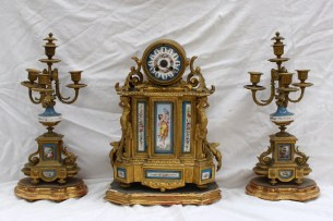 """A 19th century French gilt metal and porcelain clock garniture, the clock of drum shape supported by Caryatid figures on a plinth base, the porcelain dial with Roman numerals and flowers, the clock and candelabra inset with porcelain panels depicting figures and flowers, the clock and candelabra inset with porcelain panels depicting figures and flowers, the movement marked """" A Carlhian and Beaumetz A Paris No.4434 """"Japy Freres & Cie..."""" striking on a bell. Clock 41.5cm high, candelabra, 43cm high. Sold for £800 at Anthemion Auctions"""