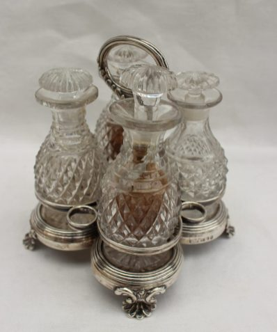 A George IV silver cruet bottle stand, with a leaf decorated ring handle, the base with line decoration on shell feet, Sheffield, 1816, Thomas & James Creswick, approximately 353 grams with four cut glass bottles. Sold for £90 at Anthemion Auctions