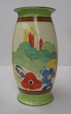 A Clarice Cliff vase of tapering cylindrical form decorated with orange towers, orange and blue flowers and green and yellow bands decorated with brown leaves to the reverse 20cms high. Sold for £240 at Anthemion Auctions