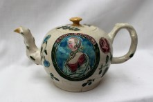 "An 18th century salt glazed commemorative teapot, decorated with a portrait of ""Charlotta Regina"", with a rose and other flowers, the other side painted with an angel on a cloud, 8.5cm high x 16cm wide, Charlotte (of Mecklenburg-Strelitz) was the German wife of King George III. She was Queen of Great Britain and Ireland from their marriage until the union of the two kingdoms in 1801, after which she was Queen of the United Kingdom .Queen Charlotte gave birth to 15 children and died in 1818. Sold for £3,500 at Anthemion Auctions"