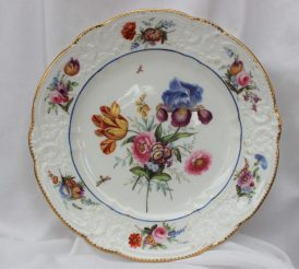 "A Nantgarw porcelain plate, with a moulded C scroll border with inset floral springs and dentil gilt rim, London decorated with a sprig of garden flowers including a tulip and Iris to the centre with scattered butterflies, impressed ""NANT-GARW, C.W."" to the base, 25cm diameter. Sold for £2,400 at Anthemion Auctions"