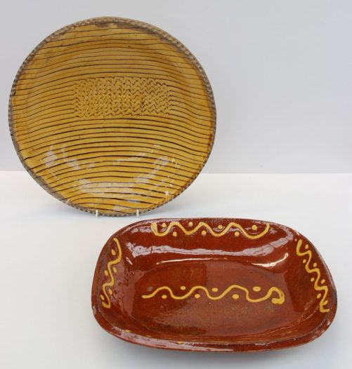 A slipware bowl with a mustard yellow glaze and line decoration, moulded with initials to the centre, 34cm diam together with another slip ware bowl of rectangular form. Sold for £2,200 at Anthemion Auctions