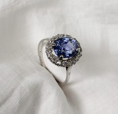 A sapphire and diamond dress ring, the central oval faceted sapphire surrounded by 18 old cut diamonds to a white metal setting and shank marked 18 plat. Sold for £2,000 at Anthemion Auctions