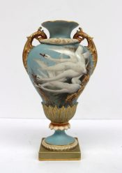 A Royal Worcester vase by Charley Baldwyn, dated 1902, of inverted pear shape with scroll handles hung with garlands coloured in coral, bronze and gold, painted with four swans in flight emerging from foliage in raised gold, set against a matt pale-blue ground, signed C H C Baldwyn, the reverse painted with a swallow in flight highlighted in gold, 20cm high, puce mark, shape number 1937, RD No.298665 (lacking cover). Sold for £1,000 at Anthemion Auctions