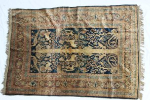 A silk rug with a central panel on a blue ground, depicting a central tree trunk with monkeys, serpents, lions, deer, peacocks and other birds, the border with interlaced floral guard stripes, 186 x 122cm. Sold for £1,750 at Anthemion Auctions