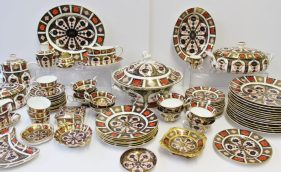An extensive collection of Royal Crown Derby 1128 pattern English Bone China comprising fourteen 27cm diameter dinner plates, an oval serving dish, 26cm wide, two oval twin handled tureens and covers, 31cm wide, an oval serving platter, 33cm wide, coffee pot, two sauce boats and stands, six plates, 21.5cm diameter, thirteen side plates, 16cm wide, two lobed dishes, 11.5cm diam, a rectangular box and cover, 11.5cm wide, a kidney shaped dish, five flared teacups decorated to the interior, six flared tea cups, three cylindrical tea cups, eight saucers, 14.5cm diameter, a table lighter, a vase and a large soup tureen and cover, 30.5cm diameter and a Royal Crown Derby espresso cup and saucer pattern No. 2731. Sold for £2,800 at Anthemion Auctions