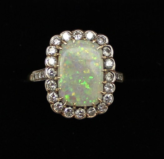 An opal and diamond dress ring the rectangular opal surrounded by twenty brilliant cut diamonds with diamond shoulders to a white metal claw setting and yellow metal shank. Sold for £620 at Anthemion Auctions