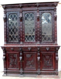 A 19th century continental carved oak bookcase, the cornice carved with lions heads and leaves above three leaded glass doors with angel carvings, the base with three drawers with lions head handles and three cupboard doors carved with figures, on a stepped base, 182cm wide x 55cm deep x 229cm high. Sold for £430 at Anthemion Auctions