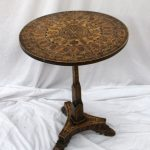 A Victorian tripod table, profusely inlaid with roundels, crosses and emblems, the pointed arched decorated column with a snap action on a trefoil base and three pad feet, 53 cm diameter. Sold for £1,250 at Anthemion Auctions