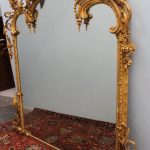 A 19th century gilt plaster overmantle mirror, the cresting festooned with scrolls, a central shield, leaves, flowers and fruit, 149 cm wide by 183 cm high. Sold for £600 at Anthemion Auctions